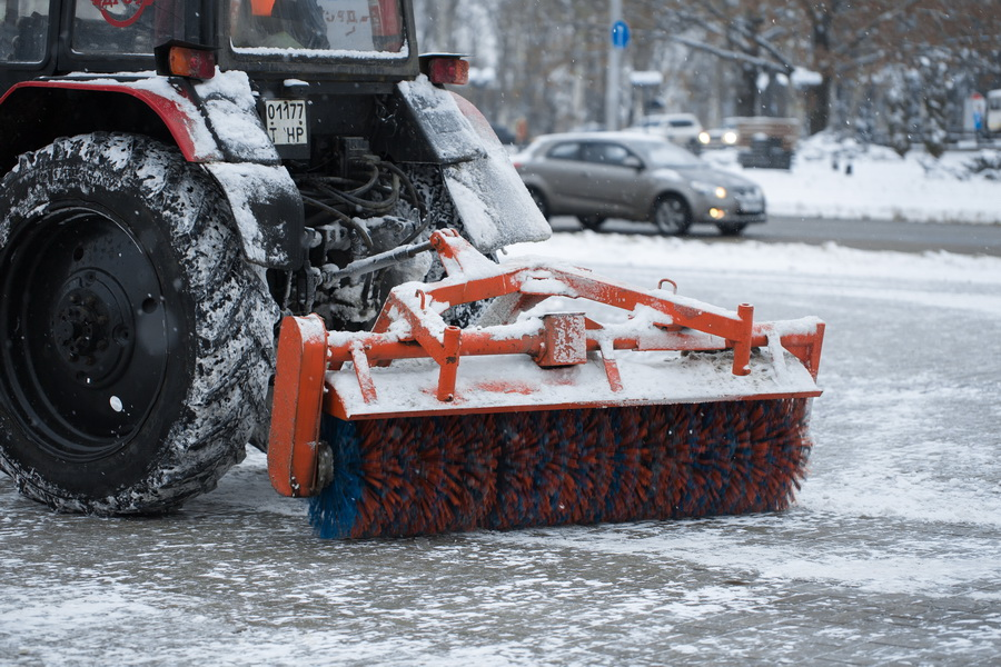 Tractor cleans snow brush