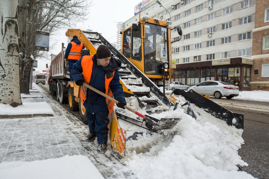 Snow-removal machine cleans the street of snow. Workers sweep snow from road in winter, Cleaning road from snow storm.